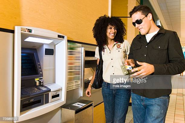 Young couple getting cash at the ATM