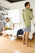 Young couple getting dressed for work in bedroom