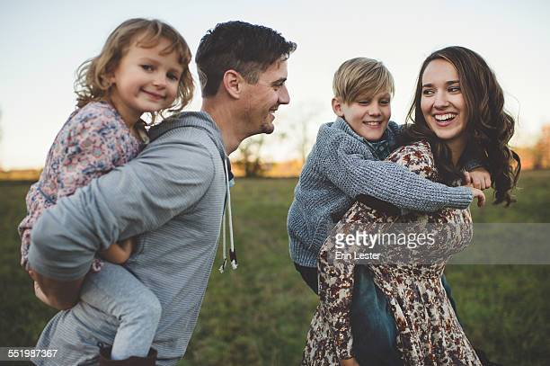 Young couple giving son and daughter piggy backs in field