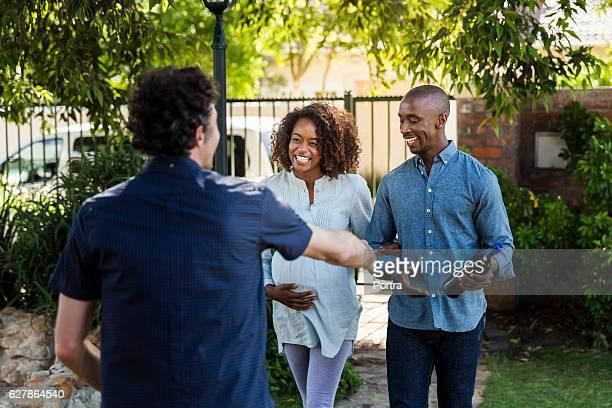 Young couple greeting man during visit at yard