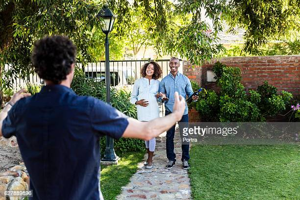 Young couple greeting man during visit in yard