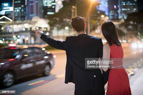 Young couple hailing a taxi on the street at night