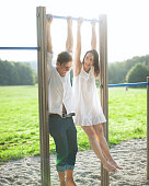 Young couple hanging on bars at playground
