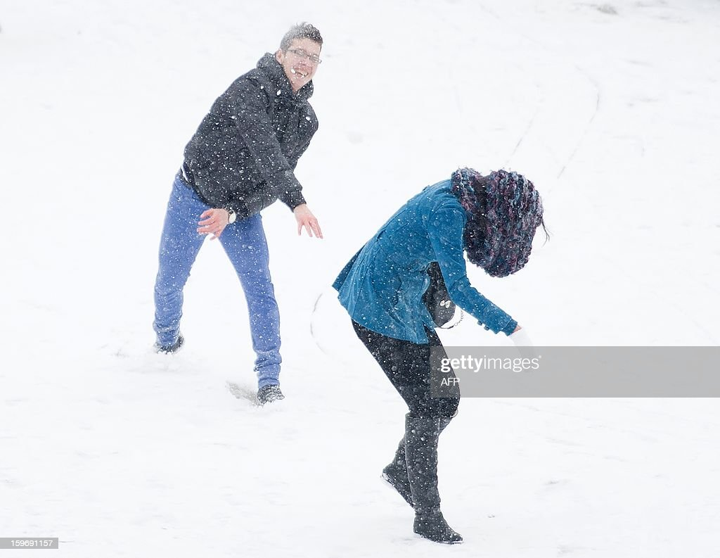 A young couple have a snowball fight on the South Bank of the River Thames near Westminster in central London on January 18, 2013. Snow swept across Britain, forcing airports to cancel hundreds of flights and more than 3,000 schools to close. AFP PHOTO/Leon Neal