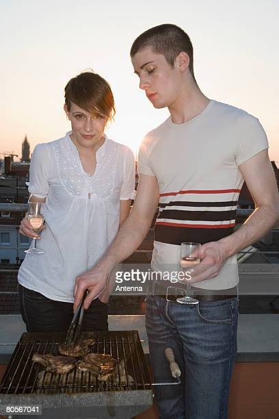 A young couple having a barbeque on a rooftop terrace