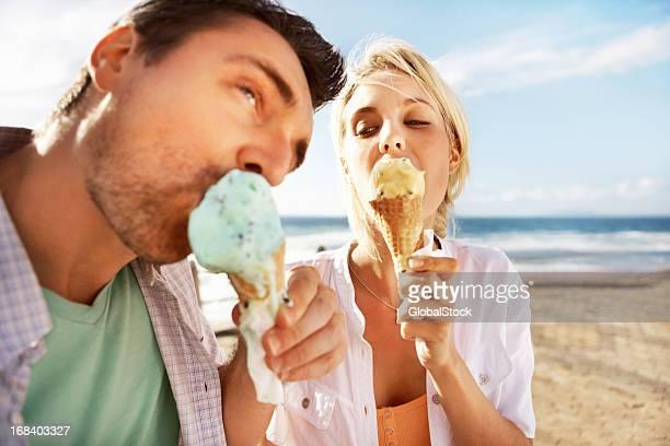Young couple having an ice cream on the beach