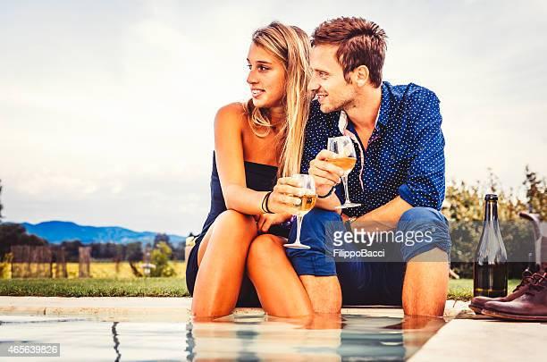 Pareja joven teniendo un aperitivo junto a la piscina