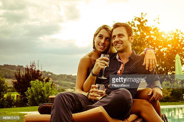 Young couple having aperitif near the swimming pool