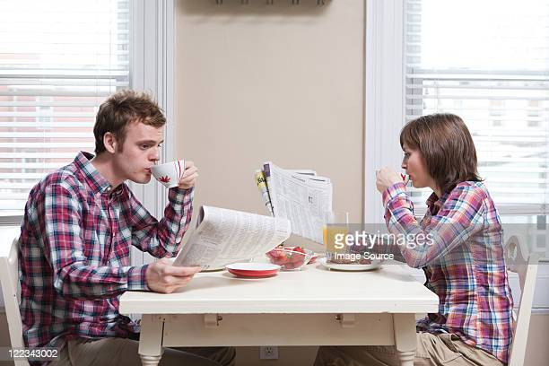 Young couple having breakfast at kitchen table