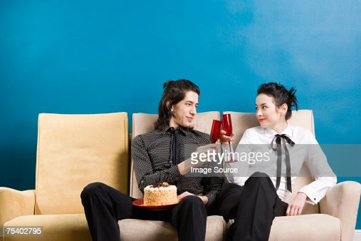 Young couple having champagne and cake : Stock Photo