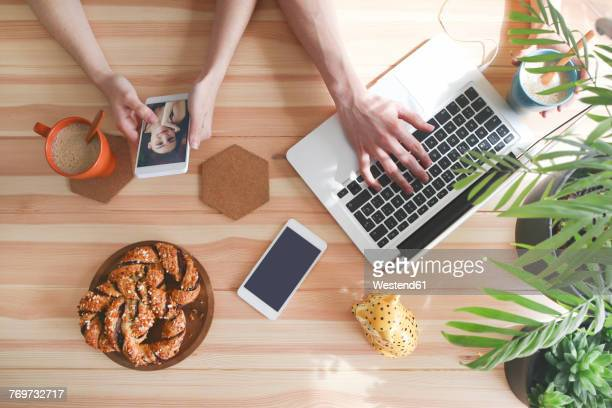 Young couple having coffee and chocolate braids using laptop and smartphone, top view