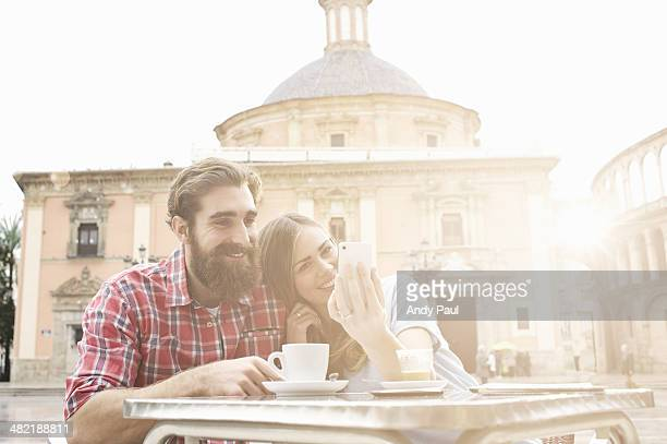 Young couple having coffee in sidewalk cafe, Plaza de la Virgen, Valencia, Spain