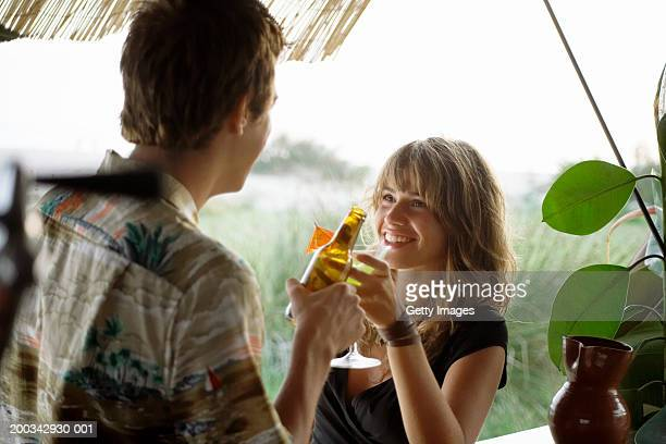 Young couple having drinks at beach bar, close-up