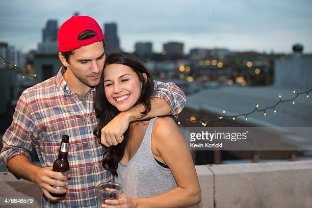 Young couple having fun at rooftop barbecue