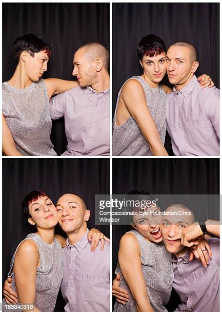 Young couple having fun in photo booth