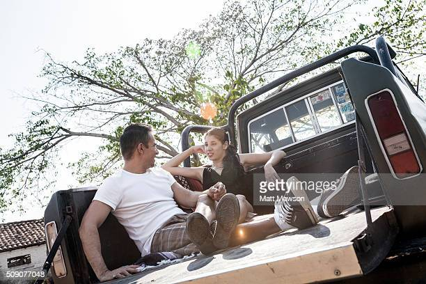 A young couple having fun in the back of a pick-up truck