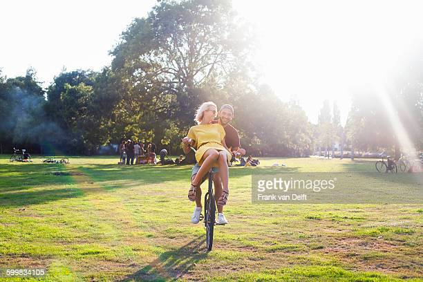 Young couple having fun on bicycle at sunset party in park