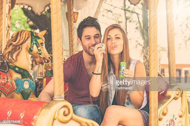 Young couple having fun on Merry-Go-Round