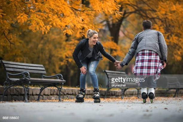 Young couple having fun on roller skates in autumn park.