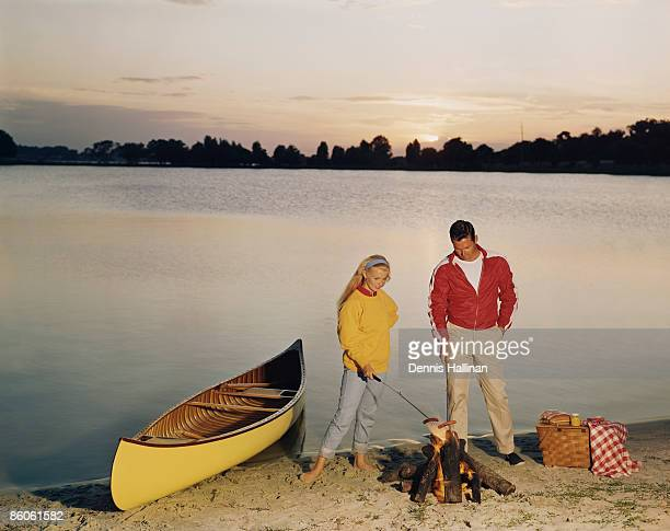 Young couple having picnic by lake at sunset