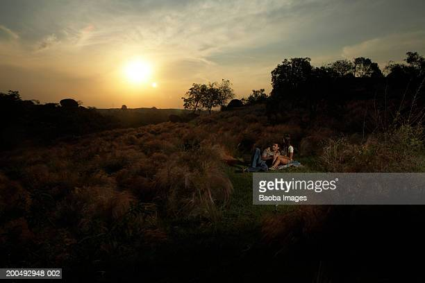 Young couple having picnic, sunset