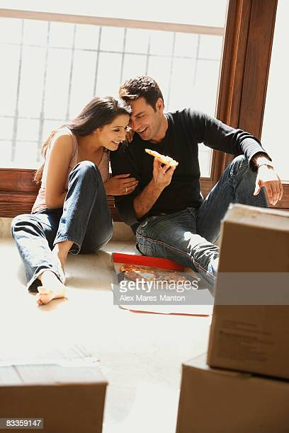 young couple having pizza on floor