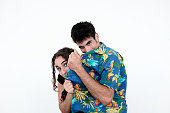 Young couple hiding their faces behind floral shirt