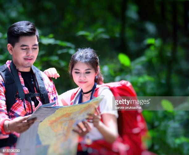 Young couple hikers in forest with backpack holding a map in the countryside .Camp Forest Adventure Travel Remote Relax Concept .