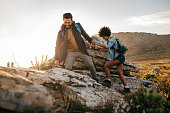 Young man helping friend to climb up the rock. Young couple hiking in nature.