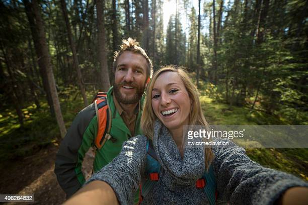 Young couple hiking in the forest taking a selfie portrait