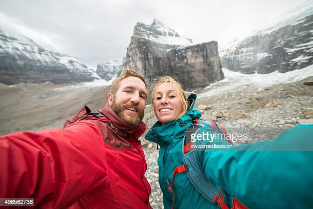 Young couple hiking on the glacier takes a selfie portrait