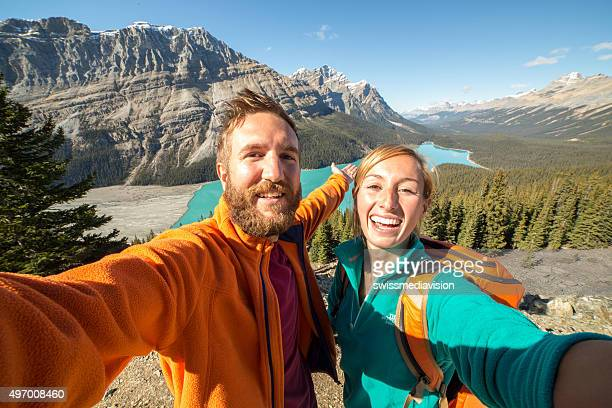 Young couple hiking reaches view point and takes selfie portrait