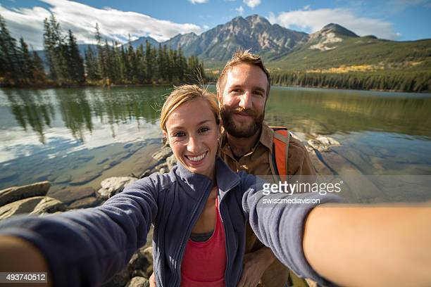 Young couple hiking takes a selfie portrait by the lake