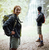 Young couple hiking to foot of waterfalls