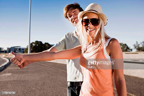 Young couple hitch hiking