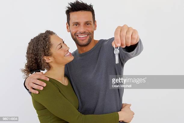 Giovane Coppia che tiene un mazzo di chiavi, isolato su bianco