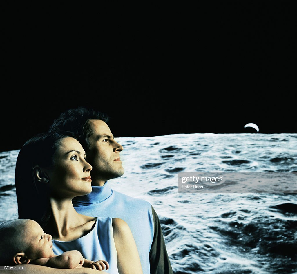 Young couple holding baby (3-6 months), against moonscape, profile : Stock Photo