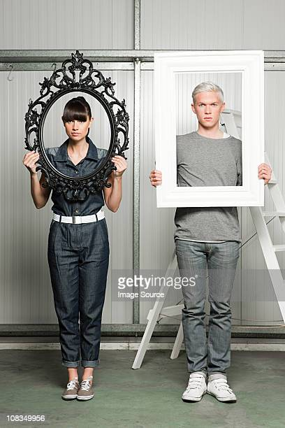 Young couple holding black and white picture frames