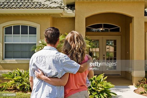 Young couple holding each other in front of a house
