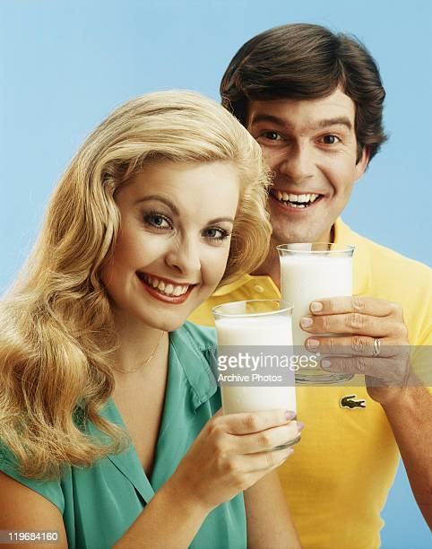 Young couple holding glasses of milk, smiling, portrait