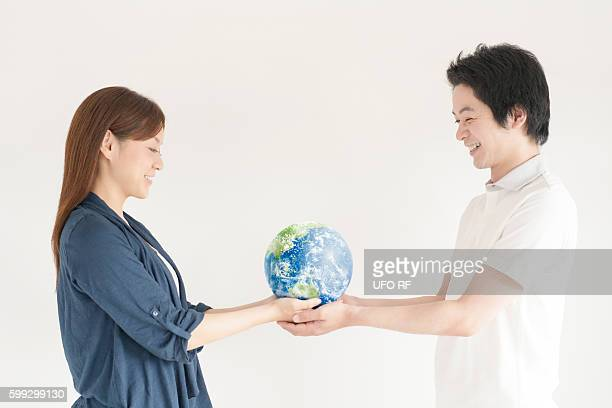 Young couple holding globe