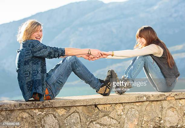 young couple holding hands and feet playfully