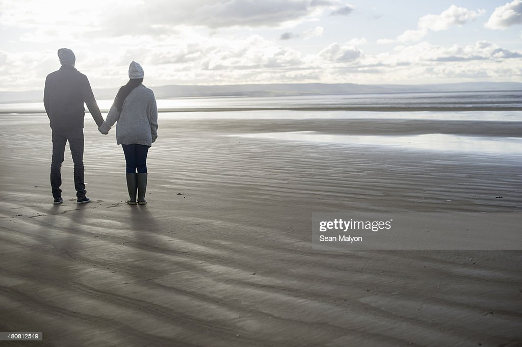 Young couple holding hands, Brean Sands, Somerset, England : Stock Photo