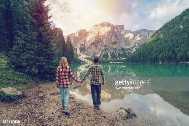 Young couple holding hands by the mountain lake, Italy