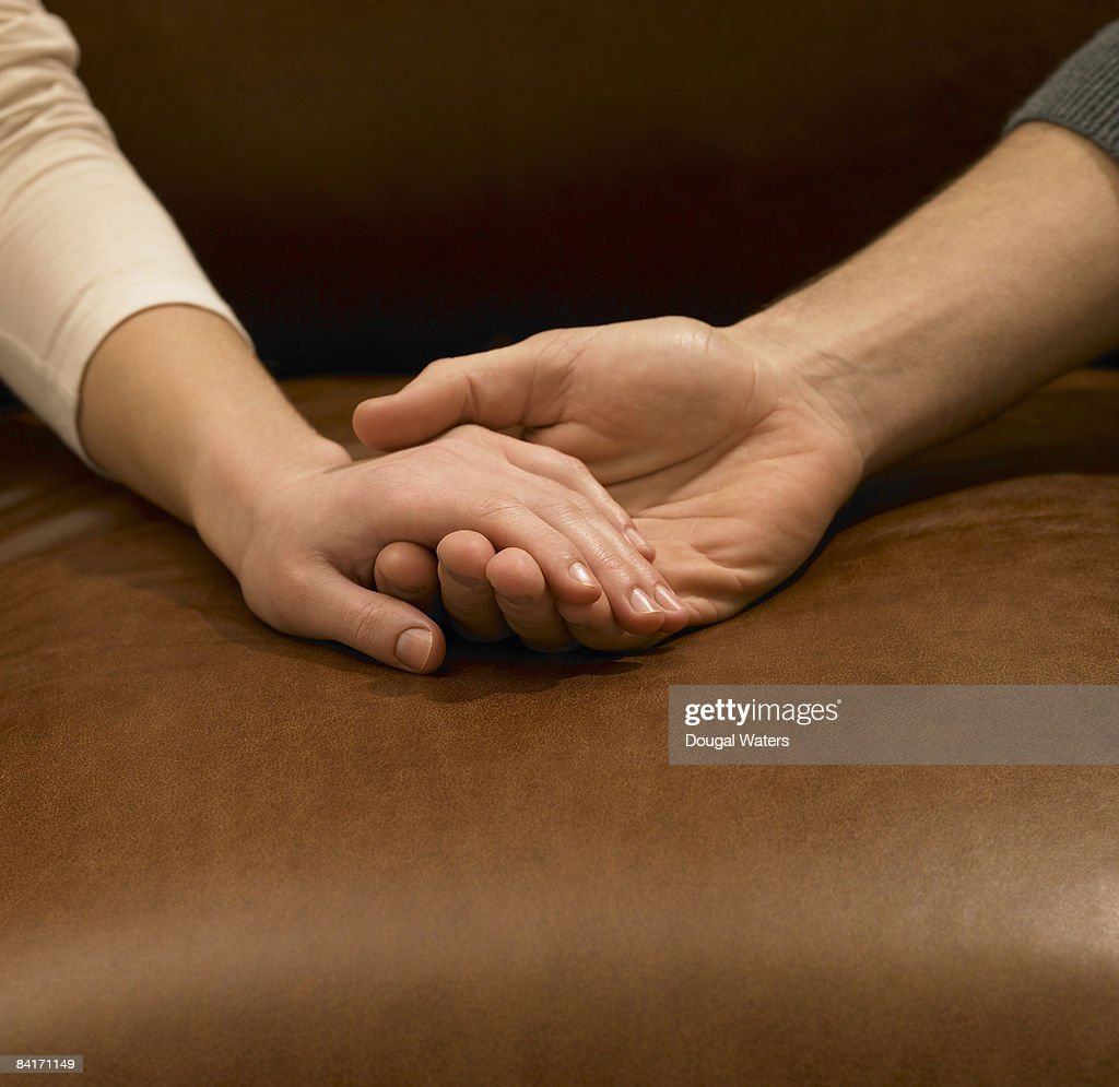Young couple holding hands, close up. : Stock Photo