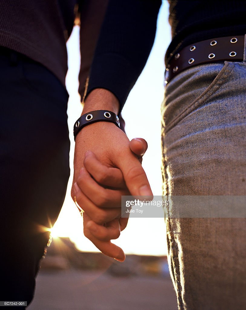 Young couple holding hands, close-up : Stock Photo