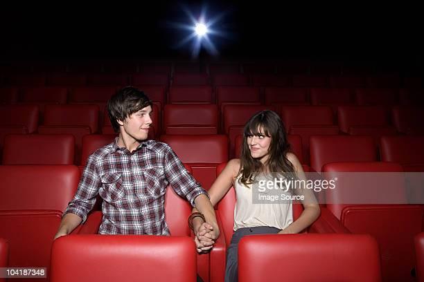 Pareja joven sosteniendo las manos en cine