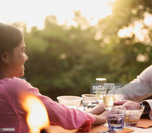 Young couple holding hands in outdoors restaurant
