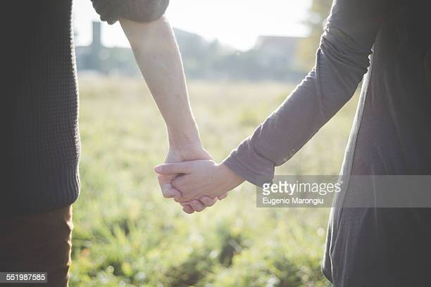 Young couple holding hands in sunlight