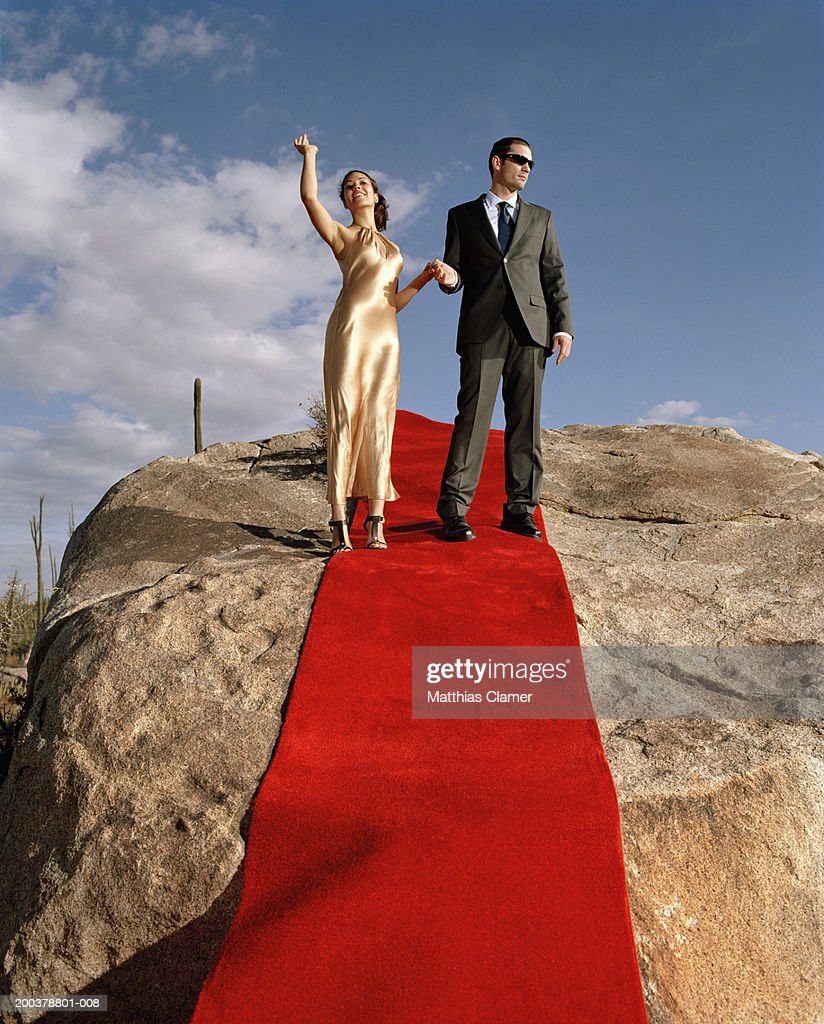 Young couple holding hands on red carpet laid on rocks, woman waving